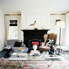 Livin groom glossy black fireplace mismatched chairs glass coffee table mismatched arm chairs high window treatments bamboo shades art