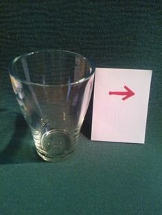 In the picture there is an arrow on a piece of card and a glass. Without turning the card around or touching it in any way, can you get the arrow to face the other direction? You can move the glass and even introduce something else to help out...