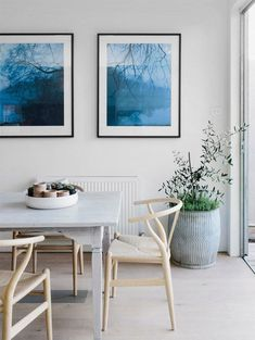 Scandinavian dining room with Wishbone chairs by Wegner, blue art, green plant.