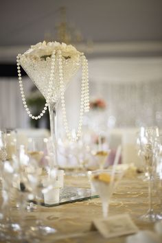 Tall Martini Glass Centre Piece With Pearls In And Draping Out If It.