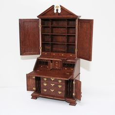 """Outstanding Georgian secretary handcrafted by Julian Biggers in 2007. Features include broken pediment crest with eagle, many interior drawers and pigeon holes, two secret compartments, two candle slides, delicately scribed pilastered upper doors, convex drawers below the drop-front writing surface, and folio partitions behind the lower doors. A grand piece 8"""" H, 3.75"""" W."""