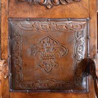 The Hoja Carved Dining Chair features beautiful, hand tooled leather.