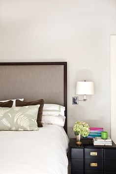 source: Mona Ross Berman Interiors website Chic bedroom features chocolate brown framed headboard accented with white and green shams as well as chocolate brown velvet pillows and green leaves pillows next to polished nickel swing-arm sconce over black nightstand with antique brass hardware.
