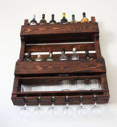 Este botellero de madera montado en la pared de madera recuperada se vería increíble en un bar de cigarros o junto a su colección de alcohol en el hogar u oficina.  Esta botella 12, 6 cristal y bolas bajo botellero de reclamado paletas. Es una manera fabulosa para mostrar tu amor por el vino y el whisky con un poco de decoración para el hogar.  Cuenta con ganchos en la espalda y le enviaremos todos los materiales de montaje para una fácil instalación.  Estamos felices de tomar órdenes de…