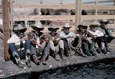 Texas - Cowboys and riders sit along a fence at the San Antonio Rodeo - 1920-1930