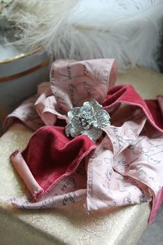 A rhinestone pin, French Script bow + soft pink and gold paper