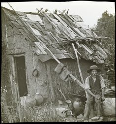 Miner Man, seated outside a wattle & daub hut, a cattle dog standing beside him. via State Library of Victoria Collections