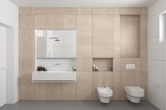 This bathroom features a light wood cabinet system that fills the wall providing storage and housing the sink, commode, and bidet.