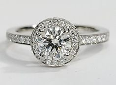 Eyes will be fixated on this immaculate platinum engagement ring, showcasing a halo design and pavé-set diamonds.