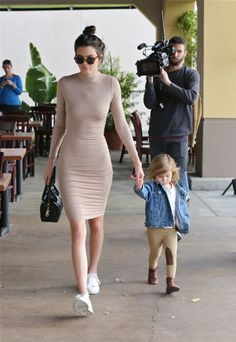 While spending the day with her niece Penelope, Jenner keeps it chic in the ultimate naked dressing staple: a flesh-toned bodycon dress. She offsets the sexy for daytime pairing it with a messy bun and trainers.
