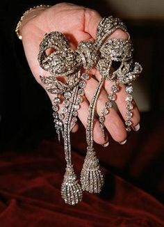 """Among the Empress Eugenie's incredible jewels is this splendid diamond bow brooch, originally part of the """"Diamants de la Couronne"""", it was made by François Kramer. The impressive bow was originally intended as a buckle for a diamond belt. Eugénie asked her jeweler to make it more elaborate, to wear it with the pair of diamond tassels. Later five diamond pampilles were added."""