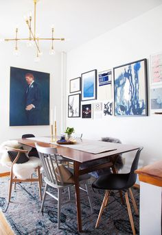 An artful dining space with gallery wall of paintings, gold light fixture, and mix and matched dining chairs