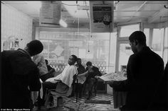 A man in a Brixton barber reads about the 1964 bout between Cassius Clay and Sonny Liston. Mr Clay was soon better known by the name Muhammad Ali