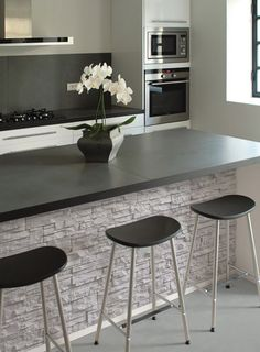 Concrete wall cladding panel like this adds texture to these kitchen area. The colour of this concrete helps the softness that the existing colour scheme has and the contrast with the dark chairs and the benchtop. Modern Kitchen Design, Interior Design Kitchen, Kitchen Decor, Kitchen Walls, Kitchen Ideas, Modern Design, Kitchen Designs, Kitchen Cabinets, Wall Cladding Panels