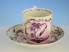 An extremely rare early Worcester Coffee Cup & Saucer, the cup with grooved strap handle, painted in puce camaieu with a peacock perched on a slender branch of a larch tree, with water in the foreground and hills in the background within puce rococo scroll work and foliate sprays.  Unmarked c1758   7,259 GBP
