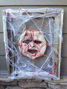 dollar store: rubber mask, frame, twine, and spider webs. Tie the mask to the frame then add the webs.