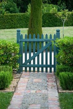 PRIVATE GARDEN, PROVENCE, FRANCE - DESIGNER DOMINIQUE LAFOURCADE. PATH WITH BLUE PAINTED WOODEN GATE