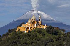 El Santuario de Nuestra Señora de los Remedios corona la Gran Pirámide de Cholula, a 10 kilómetros de Puebla. La pirámide, solo parcialmente excavada en su base, mide 450 metros de lado y 65 metros de altura, y ejerció en el pasado de centro de rituales prehispánicos. Al fondo, el volcán Popocatepetl.