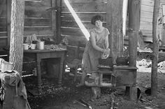 Twelve-year old girl of family of nine, cooking meal in rude, open lean-to near hut, Tennessee mydans 1936 copy