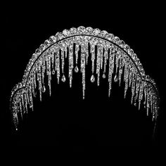 Clear image of the Chaumet ice frost tiara in gold, platinum & diamonds, created in 1904. The tiara consists of stalactite-shaped fringes; some are pointed, while others resemble melting stalactite with drops of water (in the form of pear-shaped diamonds) hanging from them. Diamond stalactites are suspended from 2 rows of brilliants hanging from a base of round diamonds.