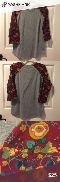 LuLaRoe Randy Tee L Gray with Maroon Print Sleeves LuLaRoe Randy Tee L Gray with Maroon Print Sleeves. Torso is light heather gray and sleeves have a floral print with maroon/burgundy background and accents in shades of gold, green, and purple. Worn twice and in excellent condition. LuLaRoe Tops Tees - Short Sleeve