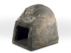 "1500-1600 ""iron bread oven with a door missing. It is rounded at the top with decorative ridges. Possibly it was a portable oven, associated with fairs."