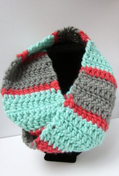 This beautiful scarf is crocheted out of thick chunky mint green, cream and coral wool. It has a wonderful thick warm texture and is warm enough to wrap around your neck twice. Scarves are the perfect fall and winter accessory. They can completely change the feel of an outfit, taking it from dressy to casual and adding a delightful pop of color. This scarf is very warm as it is made from wool and is perfect for keeping those winter drafts off your neck.  This scarf is made from wool and as…