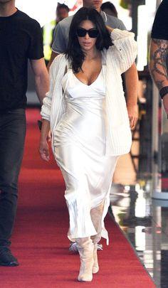 Kim Kardashian slinks into France for the Cannes Film Festival in a Calvin Klein slip dress and oversized cardigan.