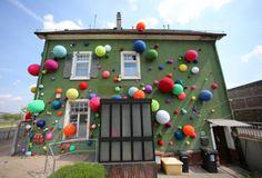 """Umgarnt: Diese Skulptur der Künstlerbewegung """"Social Knit Work"""" trägt den Namen «Haus mit Kaugummiautomat» (2014). Die bunten, gestrickten Bälle an der Fassade machen das Haus zu einem farbenfrohen Kunstwerk. Es ist teil der Kultur-Triennale. Mehr Bilder des Tages auf: http://www.nachrichten.at/nachrichten/bilder_des_tages/cme10133,1046246 (Bild: dpa)"""