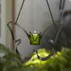 Favorite fluttery friend is ready to hang in the garden, or remove the chain for tabletop use. Green glass votive cup holds tealights and votives, sold separately. Weather-resistant metal. $12 www.partylite.biz/tenatilk