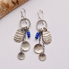 Fun fringed style earrings handmade of 925 silver and lapis lazuli beads. A cascade of different textured charms and three wire wrapped beads are suspended from chains and dangle from textured silver rings. These earrings come with my own handmade ear wires. Lightweight, yet not