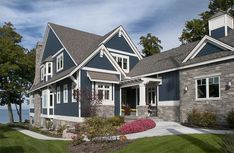 Lakefront Cottage with Coastal Interiors- pretty exterior elevation. I like the blue siding, the white trim and gray roofing and stonework. Craftsman Exterior, Craftsman Style House Plans, House Paint Exterior, Exterior House Colors, Craftsman Lake House, Cottage Exterior, Narrow Lot House Plans, Lake House Plans, Navy Blue Houses