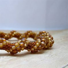 Thisbead crochet bangle bracelet is made with glass seed beads in a variety of sizes and colors.There are large bronze colored beads, medium amber beads and small translucent brown beads that cause a spiral effect.    This earthybangle is very easy to wear. Since there is no clasp you simply slide it over your hand and onto your wrist. It measures approximately 3/8 inches (.95 cm) wide and will fit on a wrist measuring up to approximately 7 inches (17.8 cm).   This bracelet is crocheted ...