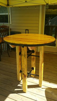 Bar height table made from reclaimed pallets, 1800's wagon wheel rim and black pipe
