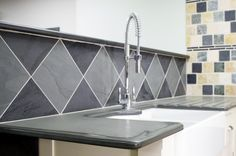 Patterned slate tiles as a sink surrond behind kitchen sink.