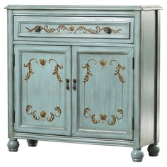 Stow your record collection in the den or keep dinnerware in the dining room with this stylish cabinet, showcasing an aged teal finish and hand-painted leaf accents.