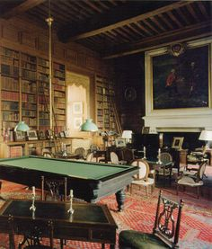 The Library at Chateau de Serrant in the Vendée region of France. It has everything a grand library should have: besides 12,000 books, there are beautiful double-height oak bookcases and paneling, a large fireplace, ancestral portraits, antique furnishings and carpets, plus a billiard table for recreation. I might never want to leave such a room.