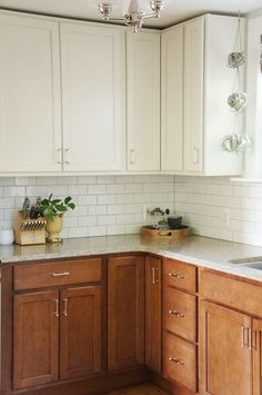 Two tone kitchen reveal- White upper cabinets, darker wood base lowers, and subway tile backsplash