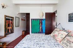 Quarto de casal tem piso de cimento queimado, quadros e roupa de cama que remete à semana de 1922.