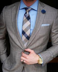 Acheter la tenue sur Lookastic: https://lookastic.fr/mode-homme/tenues/costume-chemise-de-ville-cravate/20591   — Chemise de ville bleue claire  — Broche à fleurs bleue marine  — Cravate en soie à carreaux brune  — Pochette de costume bleu clair  — Costume à carreaux brun  — Montre doré
