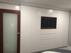 White built in wardrobe with walnut timer inset for tv