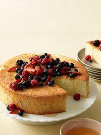 Lemon Sponge Cake with Mixed Berries - Healthy - 7 large egg whites - cream of tarter - 1 cup superfine sugar - grated lemon zest - 1 cup cake flour - 3 cups mixed fresh berries - honey - lemon juice