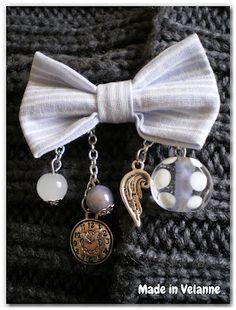 Broche noeud avec breloques aile d'ange et horloge de chez Breloque  Pendentif