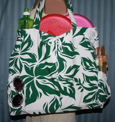Green and White floral print reusable tote bag for beach or market. Large interior and strong straps. Pockets on ends with flaps to keep your keys, glasses, phone or wallet easily accessible. This is a handmade, one of a kind bag upcycled from swim trunks. More designs at www.Etsy.com/shop/missjeansthings.  #oneofakind #upcycled #repurposed #handmade #surf #beach #surfergirl #ocean #beachwear #bikini #beachbag #grocerytote #markettote #Tote #yogabag #gymbag