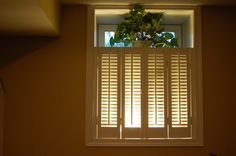 Make basement windows look bigger and add light with shutters with a light hidden behind it. I love this!