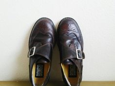 Genuine leather oxfords with topstitching, a wingtip and perforated toe and a buckle vamp. Slip-on shoe with a platform rubber lug sole.