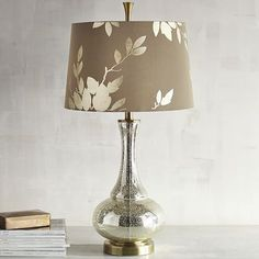 Our exclusive 3-way lamp features a champagne gold glass base in a genie shape, with a gold-lined, taupe fabric shade embossed in reflective gold-colored leaves. All so you can bring the gilded age into your home.