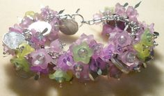 Fun and flirty cha-cha bracelet featuring purple and green lucite flowers, lots of sparkly crystals, and real pesos!  Silver plated pins and clasp, aluminum chain, so this is a very lightweight bracelet to wear.  $25.  Come visit me at www.facebook.com/nirvanabaydesigns