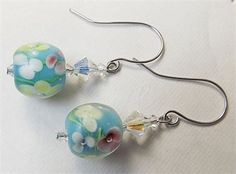 Overview  	 Handmade item 	 Materials: Stainless Steel Head Pin, Stainless Steel Ear Wires, Lampwork Bead, Czech Crystals 	Only ships within United States. 	This pair of hand made earrings features a Floral Lampwork Glass Bead with Czech Crystals including the following:  	Floral Lampwork Bead  	6mm AB Czech Crystal Bicones  	4mm AB Czech Crystal Bicones 	Stainless Steel Ear Wires on a Stainless Steel Headpin. 	This pair of earrings measures a little over 3/4 of an inch long from the first…