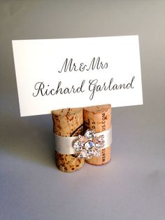 Wine Cork Place Holders (Can probably be DIY'd by glueing 2 - 3 corks together and securing them with decorative ribbon & embellishment, slicing line into top and inserting pre-printed name card)